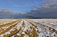 Ploughed farm land in the bacdrop as blue sky. Ploughed farm land covered with snow in winter and the blue sky in the backdrop Royalty Free Stock Photos