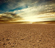 Ploughed farmland field in sunset. Ploughed farmland field on the background of cloudy sky in sunset rays royalty free stock images