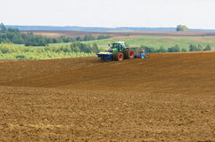 Ploughed field. Agrarian machine in a ploughed field Stock Photos