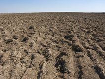 Ploughed field. View of rustic arable land on blue sky background Royalty Free Stock Photo