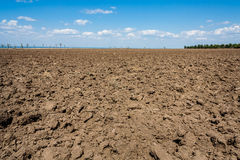 Ploughed field on the background of the blue sky. On the sea shore Stock Images