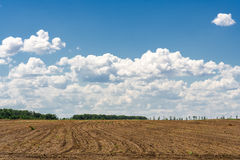 Ploughed field on the background of the blue sky. Ploughed field on the background of blue sky with clouds stock image