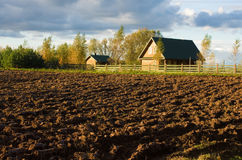 Ploughed field and house Stock Photos
