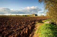 Ploughed field and house Stock Photography