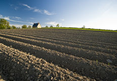 Ploughed field and house Stock Photo