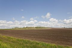 The ploughed field on a slope of a low hill Royalty Free Stock Photo