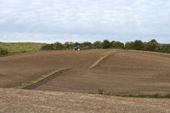 Ploughed Field. Tractor working in the field at fall. Copy space Stock Images