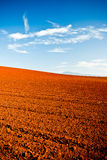 Ploughed red earth in late evening sun. Glowing richly in the golden light in a beautiful environmental landscape of agricultural land Stock Photo