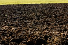 Ploughed soil in agricultural field arable land. Plowed black soil in agricultural field Royalty Free Stock Photography