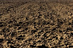 Ploughed soil in agricultural field arable land. Plowed black soil in agricultural field Stock Photo