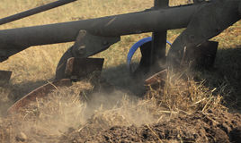Ploughing. Close-up image of plough blades during ploughing in a dry earth field. Some parts of the image present motion blur to give dynamism to the scene Royalty Free Stock Photo