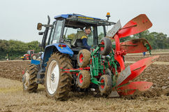 Ploughing Championship, Conventional Class. BASINGSTOKE, UK - OCTOBER 12, 2014: A competitor in the one way ploughing - reversible class on the second day of the Royalty Free Stock Photos