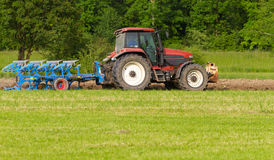 Ploughing a field. Tractor with plough ploughing a grass covered field, concept for agriculture business Royalty Free Stock Photography