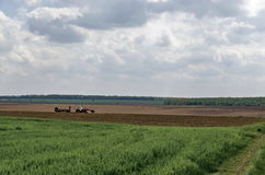 Ploughing field in spring. Tractor with trailer Stock Photos