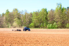 Ploughing tractor. During cultivation agriculture works at field with plough Stock Photography