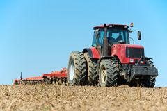 Ploughing tractor at field cultivation work Royalty Free Stock Photography