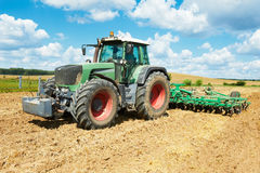 Ploughing tractor at field cultivation work Stock Photos