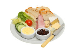 Plougmans lunch. Ploughmans lunch, bread, cheese and ham and salad with butter and pickle on a plate with a knife isolated against white stock photos