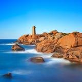 Ploumanach在桃红色花岗岩海岸,布里坦尼,法国的灯塔日落。 免版税库存照片