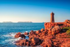Ploumanach lighthouse sunset in pink granite coast, Brittany, Fr. Ploumanach Mean Ruz lighthouse red sunset in pink granite coast, Perros Guirec, Brittany Stock Image
