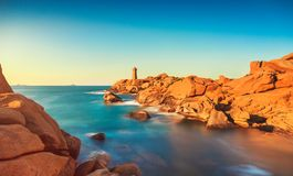 Ploumanach lighthouse sunset in pink granite coast, Brittany, Fr. Ploumanach Mean Ruz lighthouse red sunset in pink granite coast, Perros Guirec, Brittany Stock Images