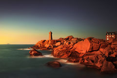 Ploumanach lighthouse sunset in pink granite coast, Brittany, Fr Stock Photo