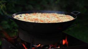Plov (a k a pilaf - le repas asiatique moyen traditionnel) est préparé sur le feu ouvert dans le camp clips vidéos