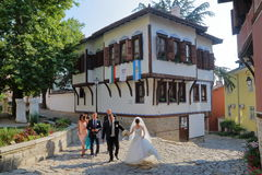 PLOVDIV, BULGARIA – JULY 18, 2015: A wedding couple with guests walking on the cobbled streets of Plovdiv Old Town. A wedding couple with guests walking on the Royalty Free Stock Images