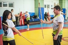 Kapap instructor Mitko Galabov teaches sticks fighting to female students stock image