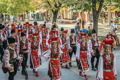 Folklore dancers in colorful costumes. Plovdiv, Bulgaria 3rd August 2013: Participants from Bulgaria in national costumes are walking on the main street of the Royalty Free Stock Photos