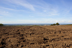 Plow soil and the vale of york. A plowed hillside field overlooking the vale of york under a blue summer sky in the yorkshire wolds Royalty Free Stock Image