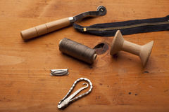 Plow, spool, zipper  and tailor tools craft concept on wooden te Stock Image
