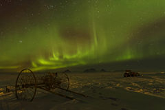 A plow under green skies of an aurora borealis Royalty Free Stock Image