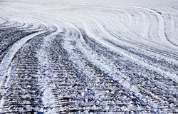 Plowed agricultural field covered with snow in winter Stock Image