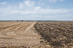 Plowed agricultural field. Plowed part of agricultural field in countryside landscape Royalty Free Stock Photography
