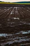 Plowed black earth horizontal landscape. Artistic landscape of plowed with water black furrows earth and dark grey sky Royalty Free Stock Photography