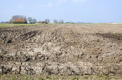 Plowed farm land. With a little village at the background Stock Images