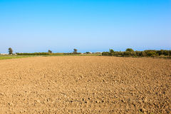Plowed field. Arable landscape, cultivated field with bare red soil under a blue sky royalty free stock photography