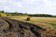 Plowed Field In Autumn. Freshly plowed field on the left showing the pattern, on the right harvested field soon to be plowed. Photographed in Tilkanen, Finland Stock Photos