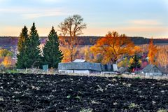 Plowed field on the background of autumn forest and old houses