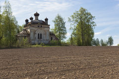 Plowed field on a background of crumbling church. Concept of rebirth of life Royalty Free Stock Photos