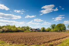 Plowed field on a background of rural houses. Landscape plowed field on a background of rural houses Stock Image