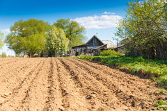 Plowed field on a background of rural houses. Landscape plowed field on a background of rural houses Stock Photography