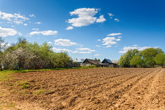 Plowed field on a background of rural houses. Rural landscape plowed ground on a sunny day Stock Photo
