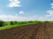 Plowed field and blue sky with clouds Stock Photo