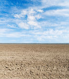 Plowed field and blue sky with clouds Royalty Free Stock Photo