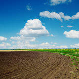 Plowed field and clouds in blue sky. Black plowed field and clouds in blue sky Stock Photos