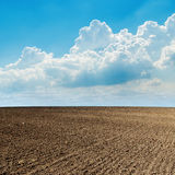 Plowed field and clouds over it Stock Photo