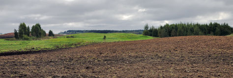 Plowed field at cloudy day Stock Photo