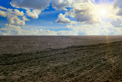 Plowed field and cloudy sky. A plowed field and cloudy sky Royalty Free Stock Photography